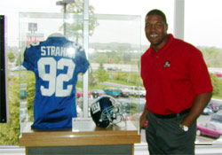 Michael Strahan poses with the jersey and helmet he wore when he set the NFL single season sack record.