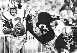 Namath scrambles from the pocket under a fierce rush by the Raiders in the famous